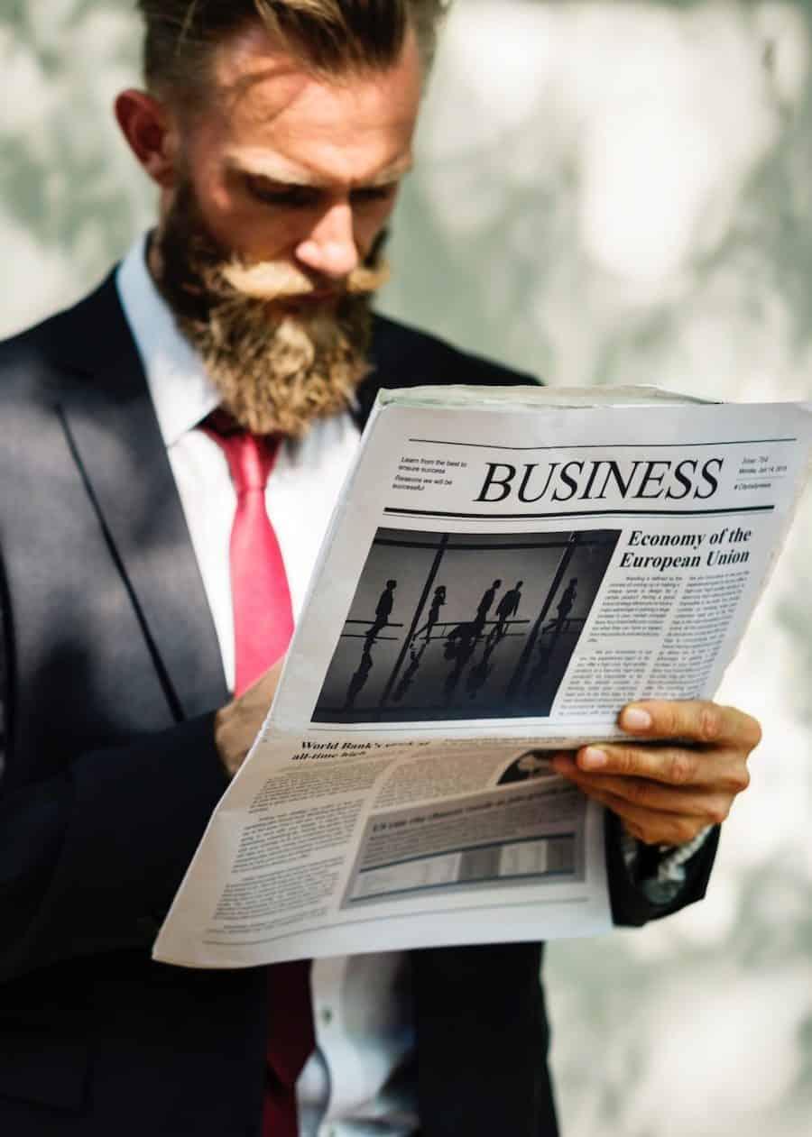 stehender Mann im Anzug mit Zeitung