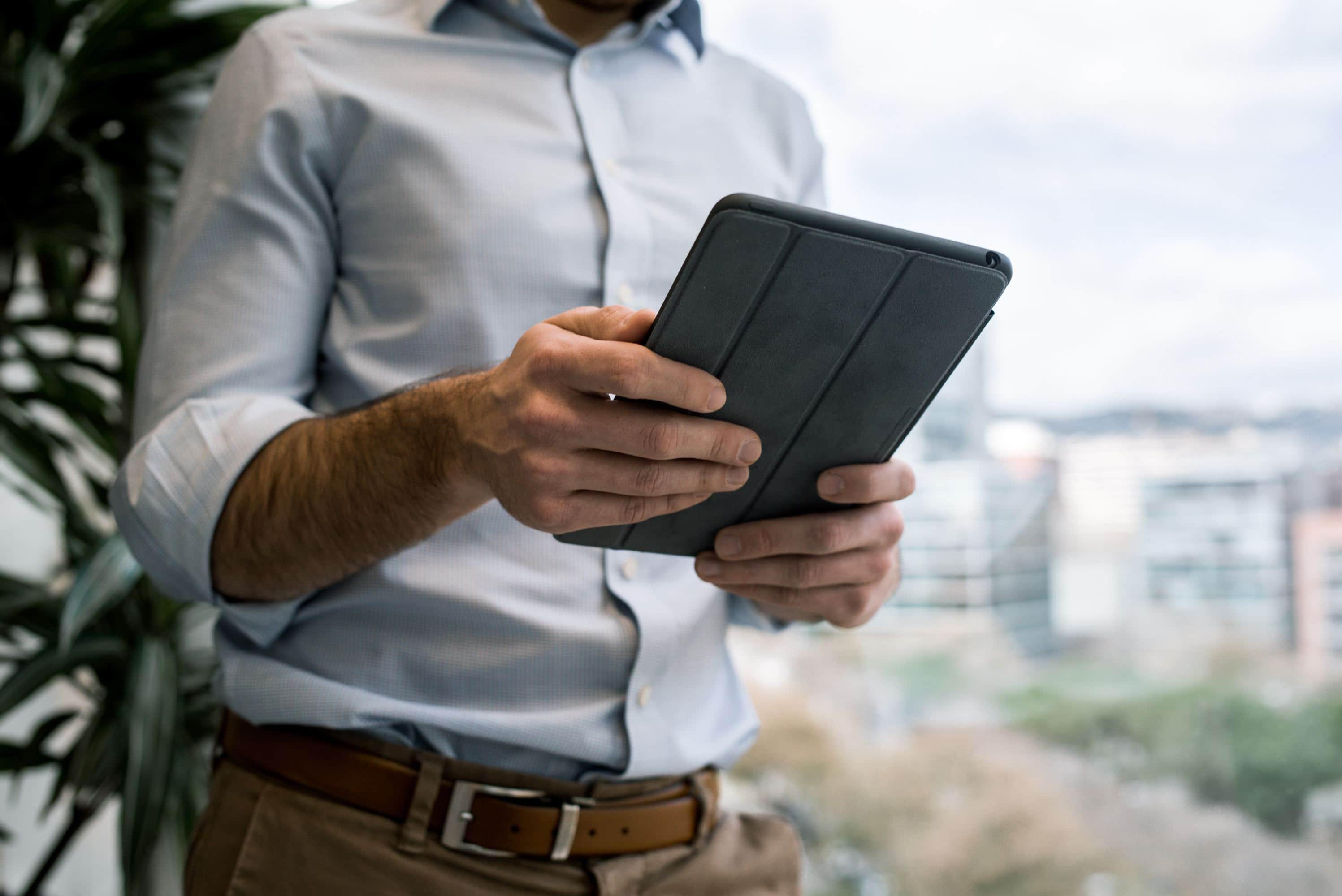 stehender Mann mit Tablet im Hemd